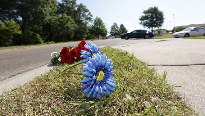 Flowers are placed along the sidewalk Sunday near the site where two Hattiesburg, Miss., police officers were fatally shot during a traffic stop the night before.