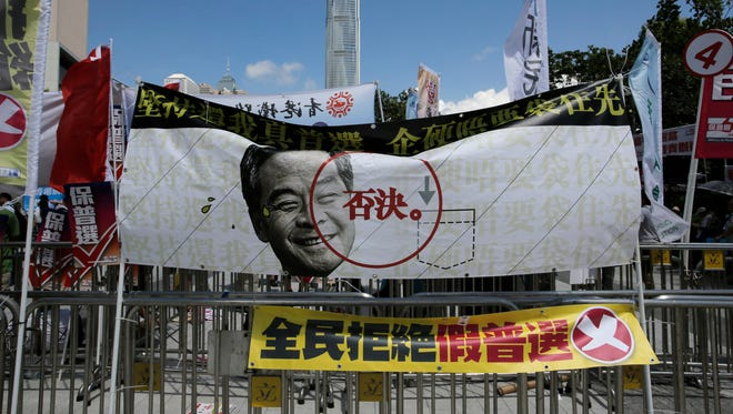 "A banner depicting picture of Hong Kong Chief Executive Leung Chun-ying with words ""Reject"" is displayed outside the Legislative Council in Hong Kong, June 18, 2015."