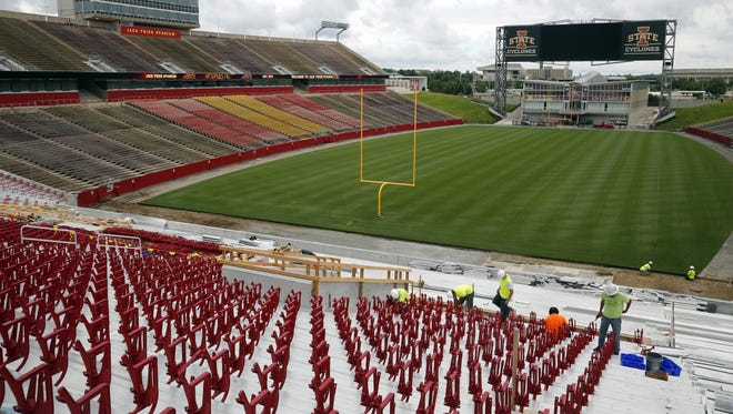 Workers install new seats as construction continues on the new south end zone project at Jack Trice Stadium in Ames Friday, June 26, 2015. Iowa State says the project will be finished in time for the Sept. 5th season opener.