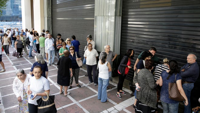 People stand in line outside a bank that operates on Saturday but eventually didn't open in central Athens on June 27, 2015.