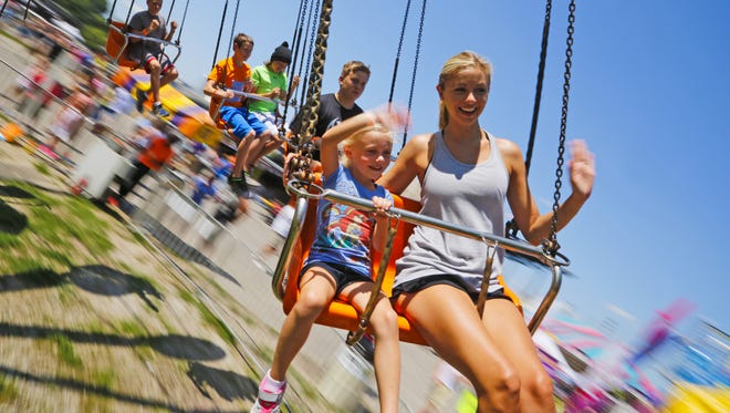 Sara Hubbell of Marion and her daughter Lola, 5, ride the Lolly Swings at the Iowa State Fair Friday, Aug. 14, 2015.