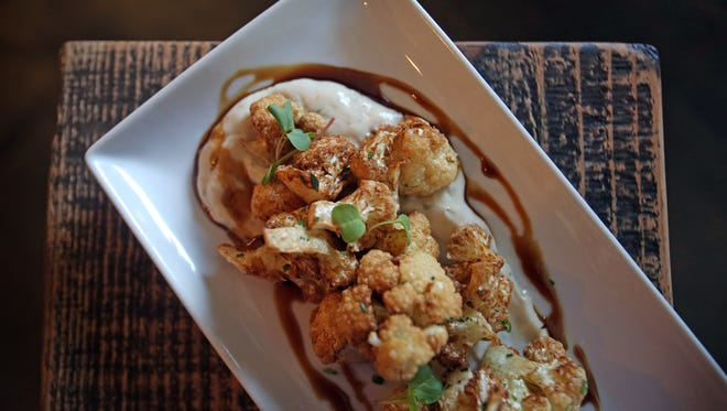 Fried cauliflower is served over yogurt tahini and pomegranate molasses at Communal Kitchen in Nyack.