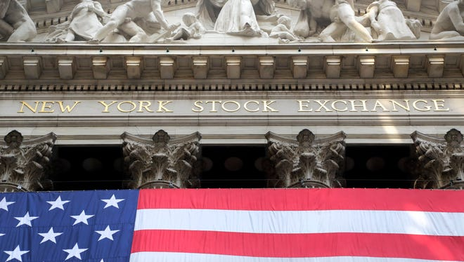 An American flag is draped on the exterior of the New York Stock Exchange. International stock markets fell Monday, Nov. 16, 2015, after attacks in Paris.