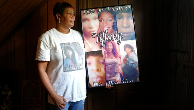 Temeka Edwards poses for a portrait in her home with a poster of her daughter, Tiffany. Tiffany Edwards, a transgender woman, was murdered in 2014. The man accused of the murder is in the Hamilton County jail awaiting trial.