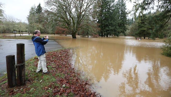 """Gerald Macke of the National Weather Service in Portland takes pictures of high water at Sarah Helmick State Park Tuesday, Dec. 8, 2015, in the Monmouth area. """"I came out to do some storm assessment and see if the rivers are as high as we think they are,"""" Macke said."""