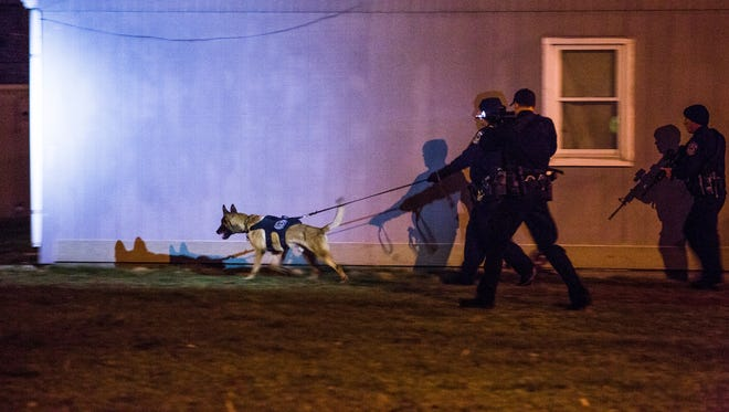 An IMPD K-9 unit searches for suspects that opened fire on police in the area near Luther and Minnesota street.