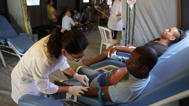 Patients receive treatment at a medical mobile unit in the Brazlandia neighborhood of Brasilia, Brazil, Wednesday, Feb. 17, 2016. The medical unit is in place to attend those who have been affected by diseases transmitted by the Aedes aegypti mosquito, like dengue, malaria and Zika.