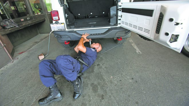 Customs and Border Protection Officer manually inspects a vehicle at the Calexico point of entry into the United States.