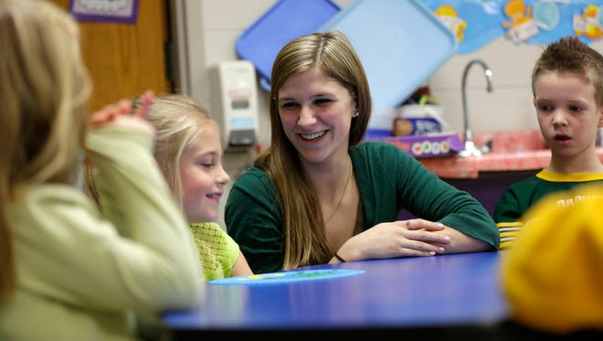 Emily Weiler smiles while tutoring Addylinn Scholl (left) and Austin Hilgart at Auburndale Elementary School March 17, 2016.