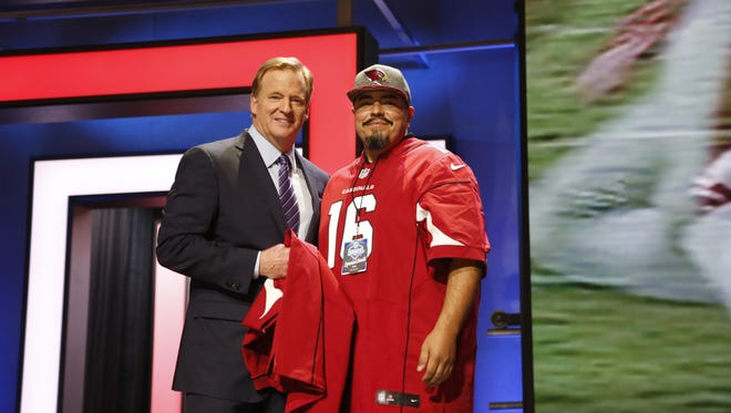 Cardinals fan Robert De La Vega, Jr. with NFL commissioner Roger Goodell on stage at the first round of the NFL draft.