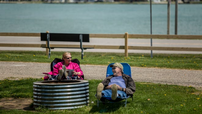 Candy and Greg Dault, of Muskegon, relax in the sun at their campsite near the St. Clair River at Algonac State Park.