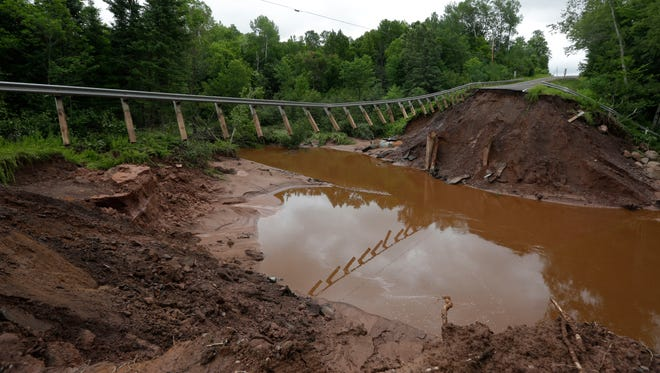 State 169 girders are suspended in mid-air over a massive washout north of Gurney, July 14, 2016.
