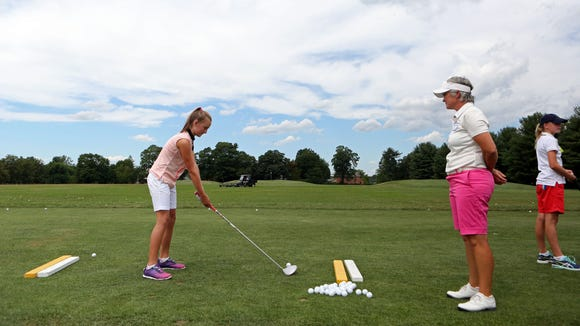 Apawamis' director of instruction Monique Thoresz looks on as Sofia Krause, 11, of Greenwich practices her swing at the Women's Metropolitan Golf Association's annual Girls to the Tee event at Westchester Country Club in Rye, Aug. 8, 2016. The free clinic, for girls ages 6-18, is an afternoon of instruction and networking to help show girls who are learning the game that they are part of a larger group.
