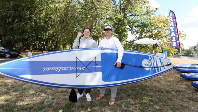 Woodward Surf Co. Owner Tod Woodward and his stepson Cole Parker, hold an inflatable stand up paddle board at Wallace Marine Park on Friday, Sept. 2, 2016. Woodward Surf Co. is offering stand up paddle board rentals Wednesday through Sunday, from now until mid October.