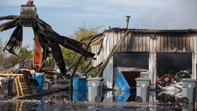 Nick Schweitzer, an employee at O'Risky Excavating, demolishes the back end of the Piranha Mobile Shredding and Recycling building after a fire in Evansville on Friday morning.