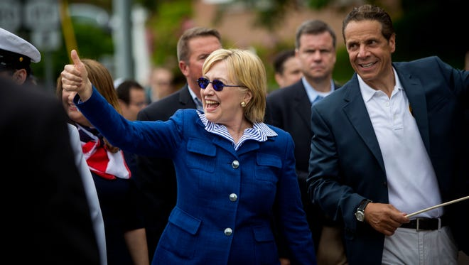 Democratic presidential candidate former Secretary of State Hillary Clinton and New York Governor Andrew M. Cuomo walk in the Memorial Day parade May 30, 2016 in Chappaqua, New York.