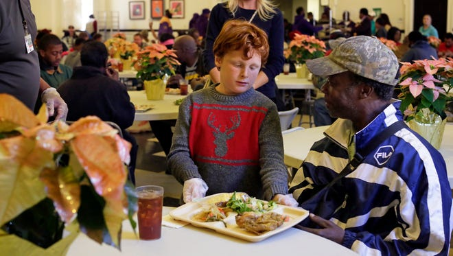 Volunteer Bailey Bryant serves meals at the nonprofit Stewpot Community Services.