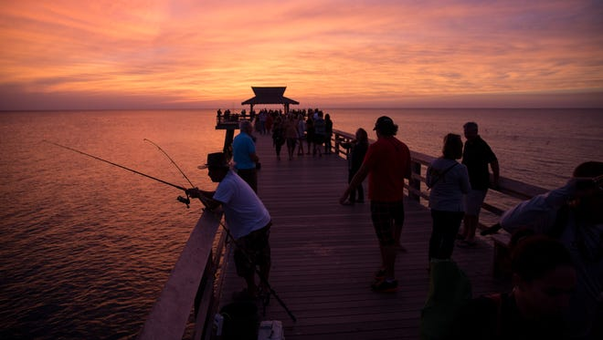 Tourists fish and take in the sunset from the Naples Pier in downtown Naples, Fla., on Wednesday, Oct. 26, 2016.