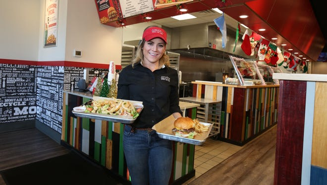 Regional manager Heather Tabachnick holds the Loaded House Salad and the Mooyah Burger at Mooyah Burger in Larchmont.