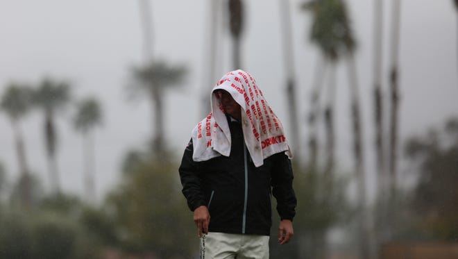 Jason Dufner covers his head from the rain at the La Quinta Country Club during the 1st round of the CareerBuilder Challenge on Thursday, January 19, 2017.