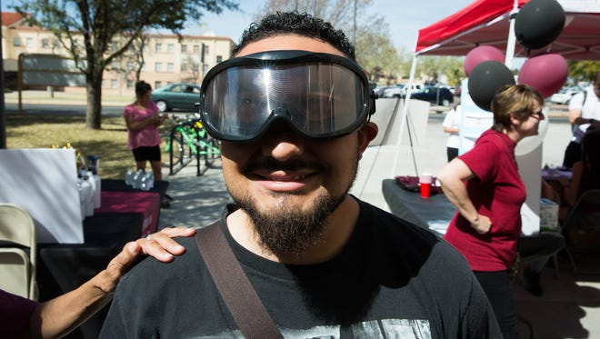 Adrian Llanez, a senior at New Mexico State University studying kinesiology, puts on drunk goggles that simulate the way a person who is over the legal limit of alcohol would see the world, prepares to try and bowl, outside the James B. Delamater Activity Center at NMSU at an event to bring awareness of binge drinking to students before spring break starts, Wednesday, March 15, 2017