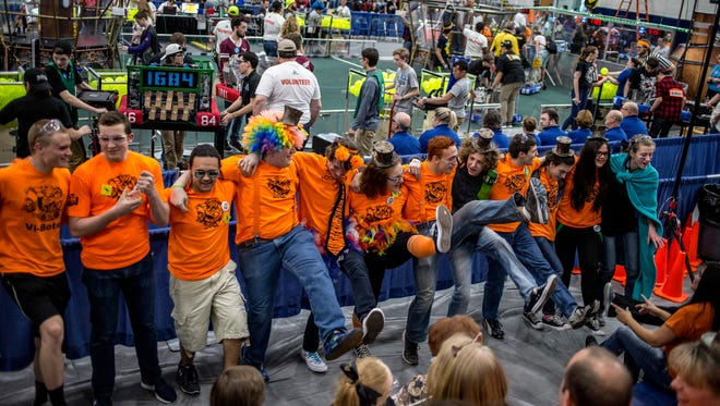Members of the Marysville Vi-Bots 5167 dance together during a 2017 FIRST Robotics District Event at Marysville High School.
