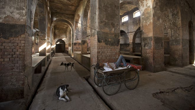 A man sleeps on a hand cart on March 31, 2017, at a slaughter house shut in the northern Indian state of Uttar Pradesh because of a crackdown by Hindu nationalists against  Muslims killing cows, which are sacred in the mostly Hindu nation.