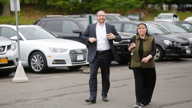 Yitzchok Ullman, councilman and deputy supervisor for the Town of Ramapo and Mona Montal, head of the purchasing department, walk into the Ramapo Town Hall in Airmont on May. 22, 2017.