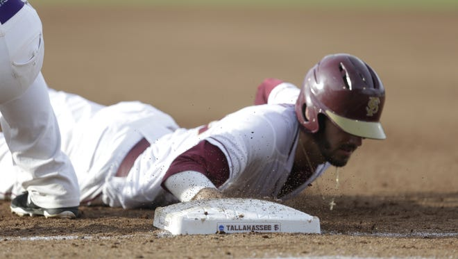 Florida State's Dylan Busby slides safely back to first during the Seminoles game with Tennessee Tech in the NCAA regionals at Dick Howser Stadium Friday night.