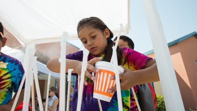 Megan Salins,7, organizes cups of lemonade at one of the two stands set up at Jardín de los Niños, Thursday, June 22, 2017. Money collected from the stands is going to the Southern New Mexico Fallen Peace Officers Memorial fund.