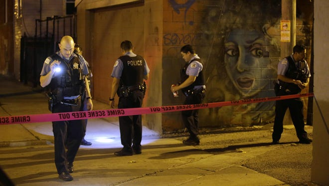Chicago Police officers investigate the crime scene where a man was shot in the alley in the Little Village neighborhood in Chicago on July 2, 2017.