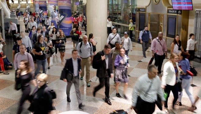 Commuters arrive in the New Jersey Transit portion of New York's Pennsylvania Station. a day after an Amtrak train was involved in a slow-speed derailment at Penn Station.