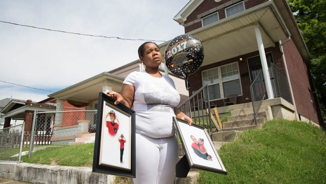 Micheshia Norment holds photos of her son, Dequante Hobbs Jr., in front of their old home where he was shot two days before he was supposed to graduate from first grade. May 22, 2017.