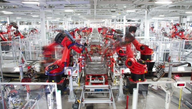 In this handout photo made available by Tesla Motors on July 3, 2017 shows robotics at work on a Telsa car at the Fremont Factory in Fremont, Calif.