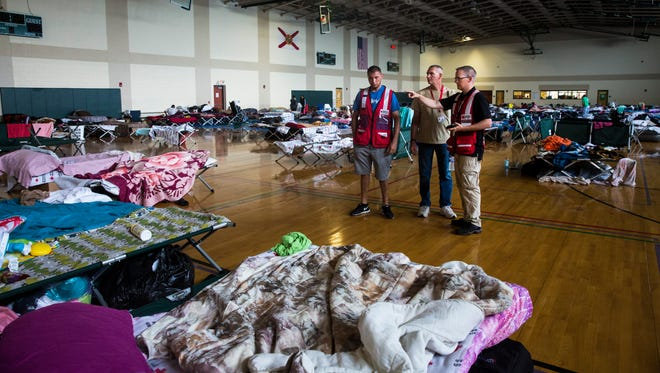 Bryan Hartmann, from right, a Red Cross shelter manager, explains some safety precautions to new volunteers Jamie Hall and Jose San Marty at the emergency shelter at the Estero Community Park Recreation Center on Sunday, Sept. 24, 2017. The Estero shelter has the largest population in the state, according to the Red Cross.