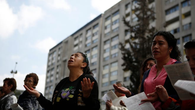 A woman prays during an outdoor Mass service, held outside Saint James Apostle Parish because the church building suffered some quake damage, in the Plaza de las Tres Culturas in Tlatelolco, Mexico City, Sept. 24, 2017.