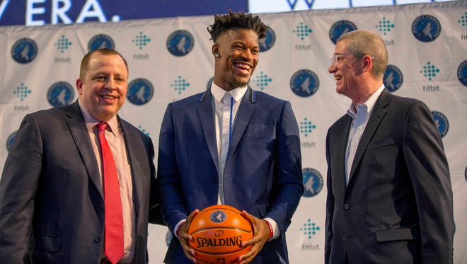 FILE - In this June 29, 2017, file photo, Minnesota Timberwolves new point guard Jimmy Butler, center, is joined by Timberwolves head coach Tom Thibodeau, left, and General Manager Scott Layden during a press conference at Mall of America in Bloomington, Minn. After a disappointing first season in Minnesota, Tom Thibodeau went to some old friends from Chicago for help. Jimmy Butler, Taj Gibson and Aaron Brooks come aboard to help the young Timberwolves get on the same page with their demanding coach.