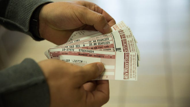 Justin Bulger, shows the tickets he bought Monday Dec. 4, 2017, at the Pan American Center Ticket Office for the Nova Home Loans Arizona Bowl. NMSU will play its first bowl game in 57 years at the Arizona Bowl, Dec. 29, in Tucson.