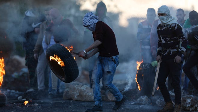 Palestinians burn tires during protests against U.S. President Donald Trump's decision to recognize Jerusalem as the capital of Israel in the West Bank town of Ramallah on Dec. 16, 2017.