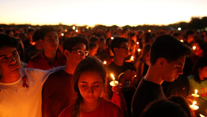 Students gather during a vigil at Pine Trails Park for the victims of the Wednesday shooting at Marjory Stoneman Douglas High School, in Parkland, Fla., Thursday, Feb. 15, 2018. Nikolas Cruz, accused of using a semi-automatic rifle in a shooting at a Florida high school, confessed to carrying out the killing and carried extra ammunition in his backpack, according to a sheriff's department report released Thursday.