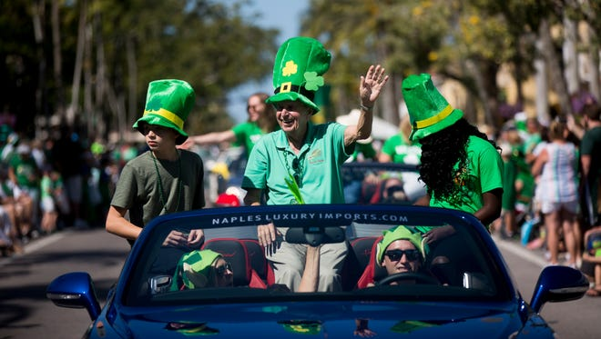 Naples mayor Bill Barnett waves to the thousands of onlookers during the annual St. Patrick's Day Parade along Fifth Avenue South on Saturday, March 17, 2018, in Naples.