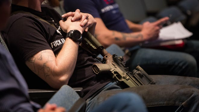 Gun rights activists, many armed with weapons entered the city council chambers after holding a protest outside of the Las Cruces City Hall, Monday March 19, 2018, protesting a City Council proposed statement of support for restrictions on Sale or possession of semi-automatic weapons.