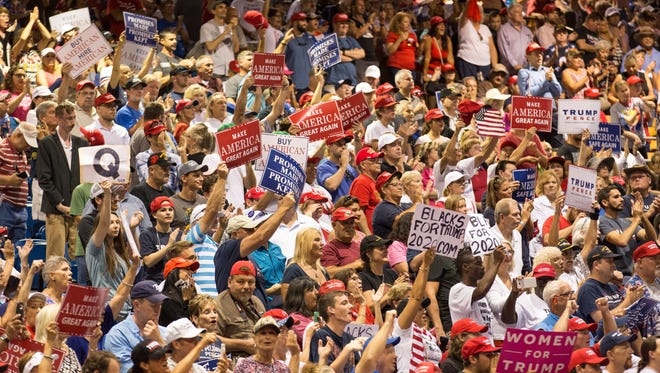 People cheer as President Donald Trump speaks at the Florida State Fairgrounds Expo Hall in Tampa, Florida, July 31. A sign showing the letter Q can be seen. Q stands for QAnon, a conspiracy theory believed to have originated in 2017.