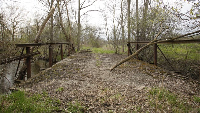An old concrete and iron bridge spans Johnson Creek, the dividing line between two parcels of land near the former Detroit House of Corrections facility in Plymouth. A judge has ruled in favor of the City of Detroit in its dispute with Plymouth Township over ownership of a portion of the site, worth millions of dollars.