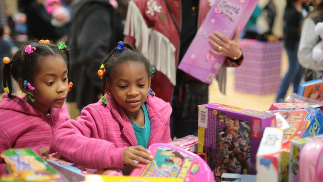 Areyna Stewart, 7, right, and her sister Laelah Stewart, 6, pick out toys during the annual toy giveaway at the Coachella Valley Rescue Mission on Saturday in Coachella.