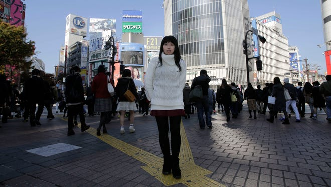 In this Friday Nov. 21, 2014 photo, Kaori Endo, a 21-year-old bread factory worker from Ibaraki, north of Tokyo, poses for a portrait at a scramble crossing at Shibuya shopping district in Tokyo.