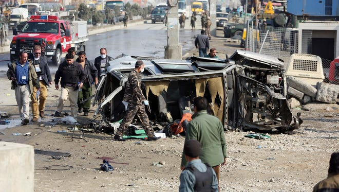 Afghan security forces inspect a British embassy vehicle which was targeted in a suicide attack in Kabul, Afghanistan.