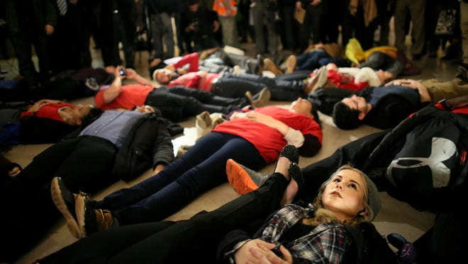 Lindsey Ellefson, 22, lies down during a protest in Grand Central Terminal December 3, 2014 in New York. Protests began after a Grand Jury decided to not indict officer Daniel Pantaleo. Eric Garner died after being put in a chokehold by Pantaleo on July 17, 2014. Pantaleo had suspected Garner of selling untaxed cigarettes.