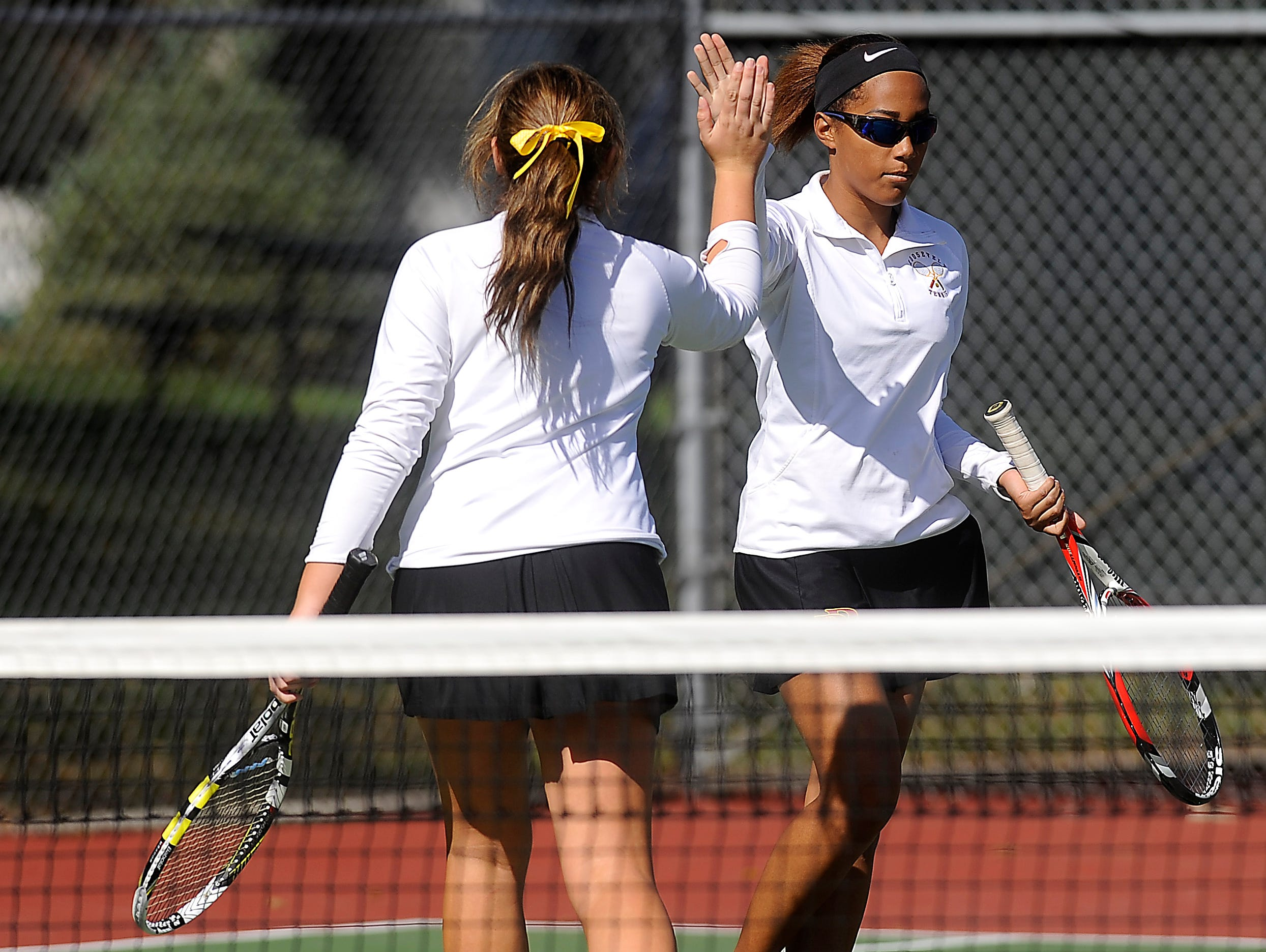 Roosevelt's Morgan Johnson and Lexy Ronning high five during doubles third round championship of the SD high school girls state tournament at McKennan Park in Sioux Falls, SD; Friday, Oct. 9, 2015.