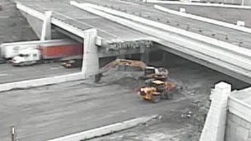 Crews remove damaged sections of the Rockville Road bridge over I-465 on Wednesday.